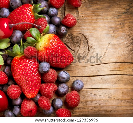 Berries on Wooden Background. Summer or Spring Organic Berry over Wood. Strawberries, Raspberries, Blueberry and Cherry. Agriculture, Gardening, Harvest Concept - stock photo