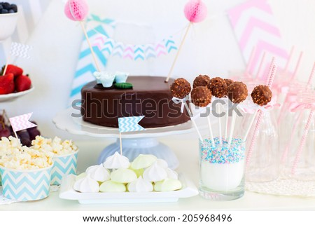 Berries, popcorn, canapes, candies and a chocolate cake on a dessert table at party - stock photo