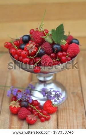 Berries red and black currants, raspberries, strawberries in a metal bowl - stock photo