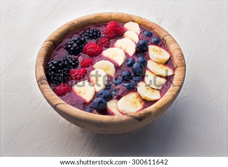 berry acai smoothie bowl with bananas, raspberries, blackberries and blueberries in a wooden bowl  - stock photo