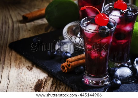 Berry alcoholic cocktail with a cherry, blueberry, honey, cinnamon, lime juice, liqueur and ice, vintage wooden background, selective focus - stock photo