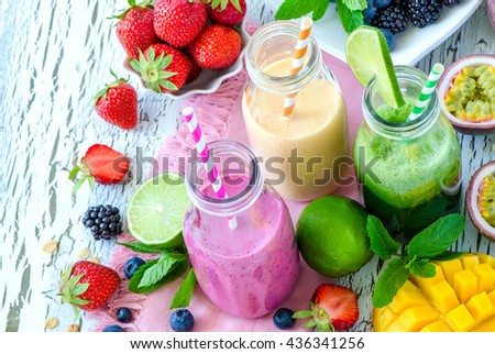 Berry and fruit smoothie in bottles, healthy summer detox yogurt drink, diet or vegan food concept, fresh vitamins, mango, lime, passtion fruits - stock photo