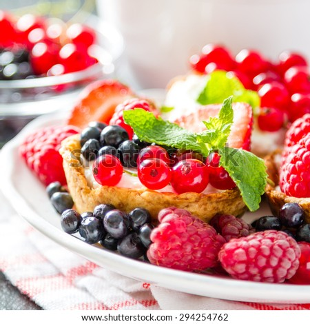Berry cakes on white plate with tea, plaid napkin, dark stone background