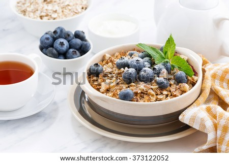 berry crumble with oatmeal in a ceramic form on white table, horizontal