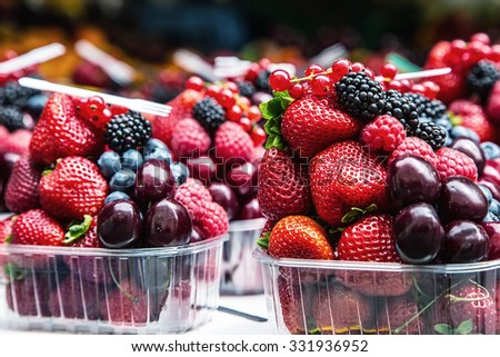 Berry fruits at a marketplace Blueberries, raspberries, strawberries, cherries Forest fruits. Gardening ,agriculture,harvest and forest concept. - stock photo