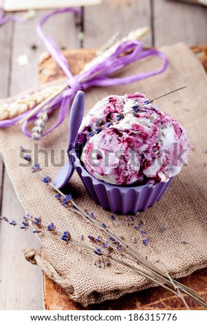 Berry  ice cream with a lavender flower decoration in a ceramic bowl on a textile and wooden background. Provence style. - stock photo