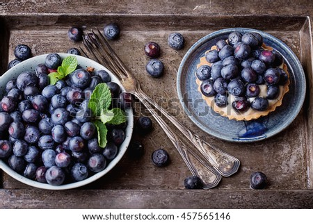 Berry mini tarts with the berries served in a bowl over a rustic metal board, top view