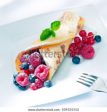 Berry pancake sprinkled with sugar with an assortment or ripe raspberries, redcurrant and blueberries garnished with mint - stock photo
