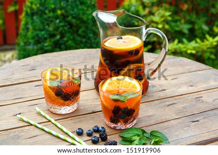 Berry sangria - cold summer cocktail, decorated with berries, orange and mint - stock photo