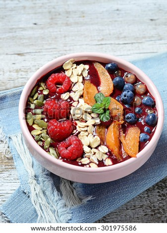 Berry smoothie bowl with raspberry, blueberry, oatmeal, apricot. Selective focus - stock photo