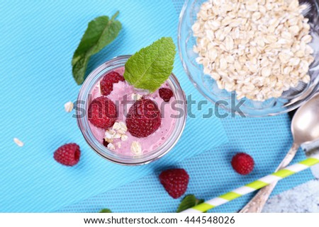 Berry smoothie yogurt with oat flakes and mint leaves for breakfast. Jar with milkshake with raspberries, green straw on the table. Delicious and healthy breakfast - stock photo