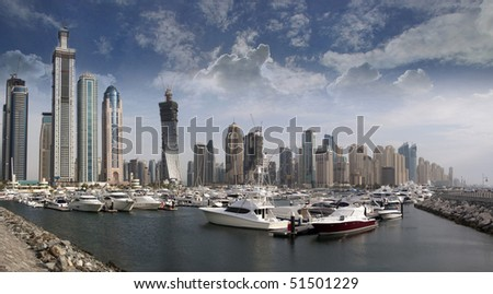 Berthing space in Dubai Marina, with several boat and yachts parked in front of the famous Marina district in Dubai, UAE. - stock photo