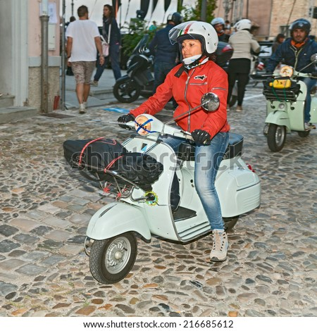 "BERTINORO, ITALY - SEPTEMBER 6: biker woman riding a vintage italian scooter Vespa during the rally coast to coast ""In Vespa dall'alba al tramonto"" on September 6, 2014 in Bertinoro, FC, Italy"