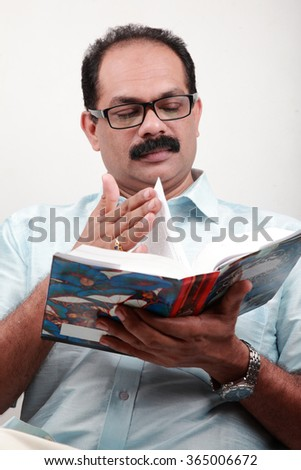 Bespectacled man reads a book in his hand - stock photo