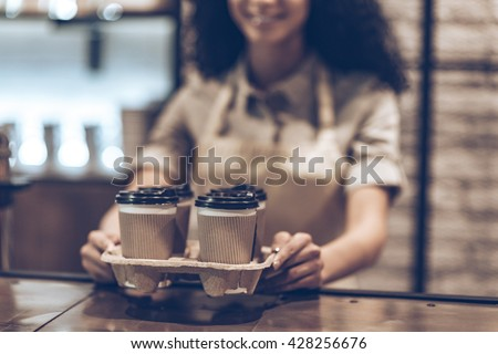 Best coffee to go! Part of young cheerful African woman in apron holding coffee cups while standing at cafe - stock photo