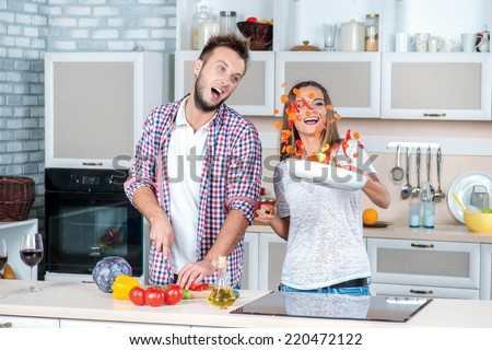 Best cooking together. Young and beautiful couple in love cooking meals in the kitchen and look at each other while standing in the kitchen and throw the food in the pan - stock photo