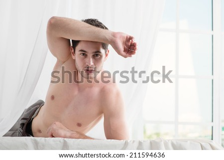 Best day morning. Stripped handsome man lying in bed with a naked torso. Young boy lying in bed with his pants unbuttoned.