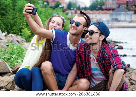 Best day of my friends. Three friends sitting and laughing at the river and pictures of each other on a cell phone - stock photo