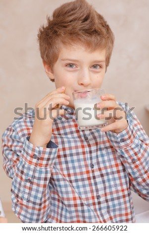 Best drink. Close-up of a cute boy in plaid shirt drinking a glass of milk and smiling at a camera - stock photo
