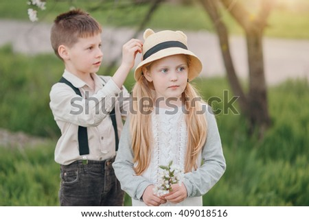 best friends a little boy in jeans with suspenders and a blond girl in a hat - stock photo