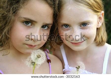 Best Friends blowing dandelions - stock photo