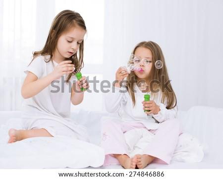 Best friends.Closeup portrait of two little sisters blowing a soap bubbles. - stock photo