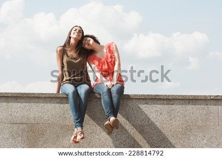 Best friends. Emotional portraits of beautiful brunettes on background of clouds. Pleasant emotions, happy mood. Female friendship. City street - stock photo