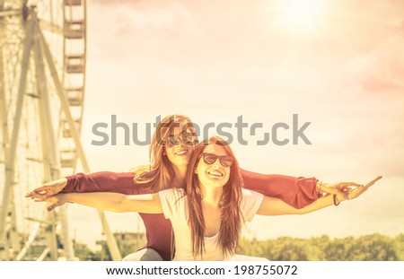 Best friends enjoying time together outdoors at ferris wheel - Concept of freedom and happiness with two girlfriends having fun - Vintage filtered look - stock photo