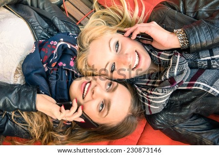 Best friends enjoying time together outdoors with smartphone - Concept of new technology with two girlfriends having fun on a vintage wood bench and red pillows - stock photo