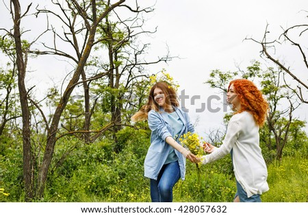 Best friends forever. Friends holding hands. BFF. A girl holding a bouquet of wildflowers. A wreath of flowers on the head of the girl. Soft focus - stock photo