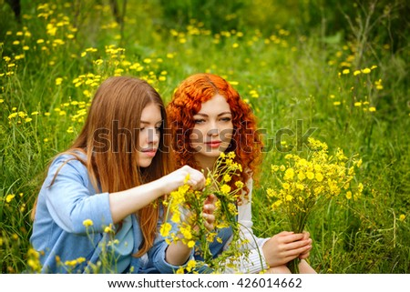 Best friends forever. Girlfriends collect bouquets of wildflowers. BFF. - stock photo