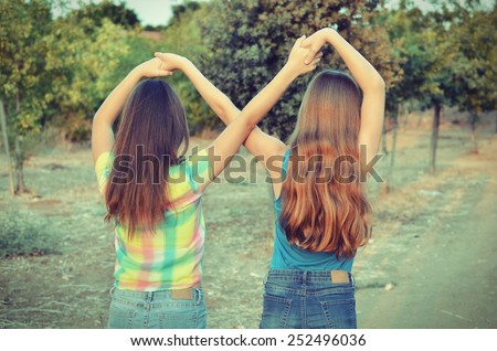 Best Friends Forever - two 12 year old teenage girls  holding hands in an infinity forever sign to signify BFF - vintage look - stock photo