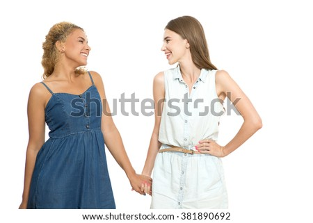 Best friends forever. Waist up portrait of two beautiful young girls standing looking at each other smiling and holding hands, isolated on white background - stock photo