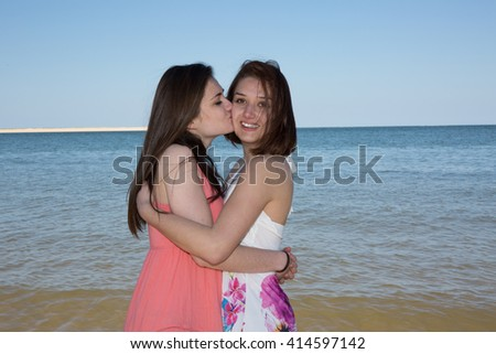 Best friends girls playful in the water at the beach