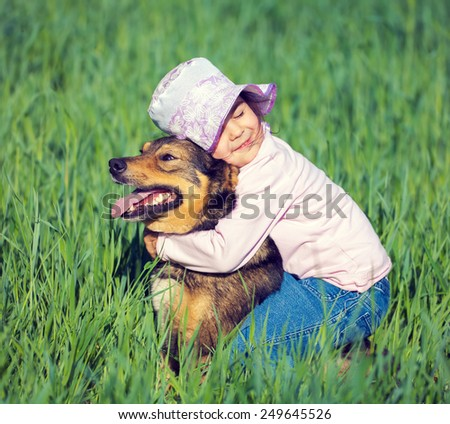 Best friends. Happy little girl hugging dog, sitting on the grass - stock photo