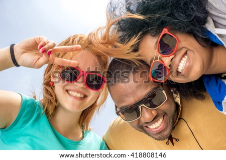 best friends having fun with toothy smile for picture looking at camera with bright sky background - concept of cross-culture friendship forever - stock photo