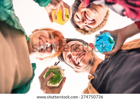 Best friends in a circle smiling together at the camera - Happy young people drinking multicolored cocktails - Concept of fun and social gathering - Shallow depth of field with focus on the guy eyes - stock photo