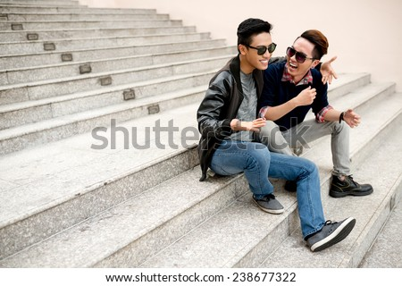 Best friends in sunglasses sitting on the steps and laughing - stock photo