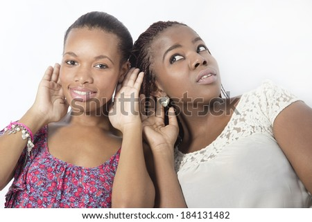 Best friends listening holding their ears hearing sound - stock photo