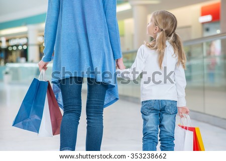 Best friends. Pleasant happy mother and daughter holding hands of each other and walking along mall while having shopping - stock photo