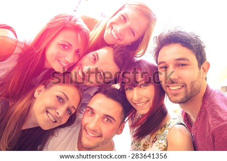 Best friends taking selfie outdoors with back light contrast - Happy friendship concept with young people having fun together - Vintage filtered look with marsala color tones and sunshine halo flare - stock photo