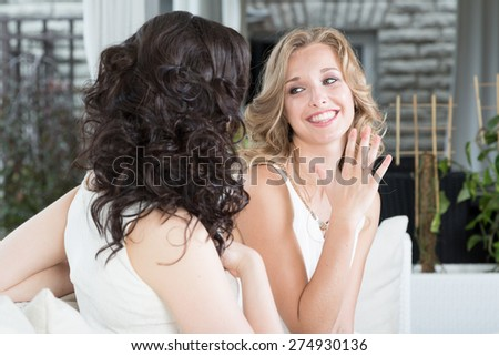 Best friends talking about relationship, woman showing engagement ring to her friend.  - stock photo