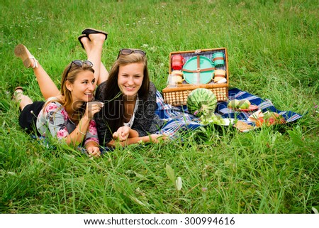 Best friends - two attractive young girls are having a picnic, dressed casual lying on the lawn in summer. One girl is teasing the other with a blade of grass, having fun. - stock photo