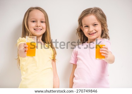 Best friends. Two cute little girls holding juices on grey background. - stock photo