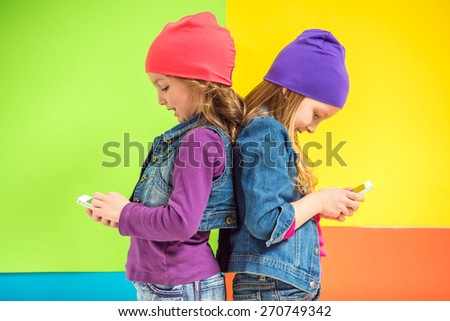 Best friends. Two cute little girls using phone on colorful background. - stock photo