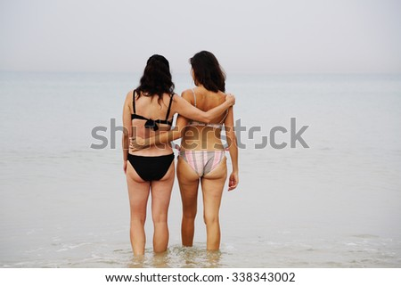 best friends walking at seaside - stock photo