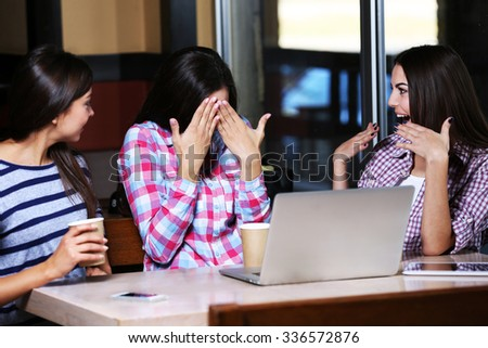 Best friends with laptop together sitting in cafe