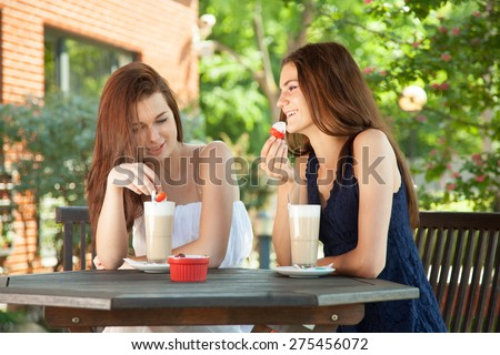 Best friends - young women sitting in summer cafe, drinking latte and talking to each other.  - stock photo