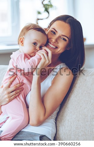 Best hug ever. Cheerful beautiful young woman holding baby girl in her hands and looking at camera with smile while sitting on the couch at home - stock photo