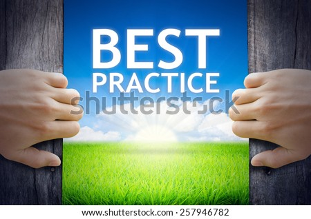 Best Practice. Hand opening an old wooden door and found Best Practice word floating over green field and bright blue Sky Sunrise. - stock photo